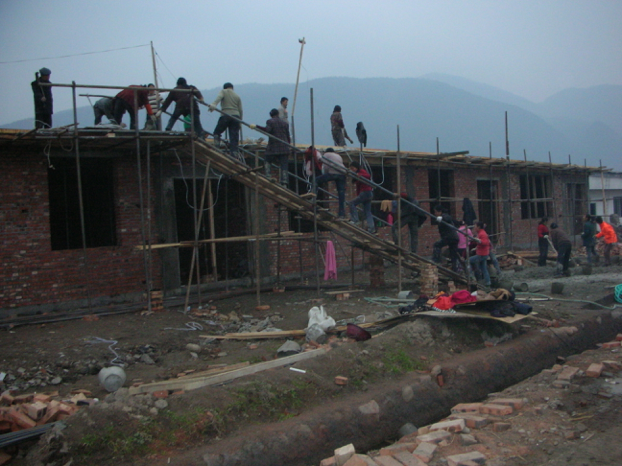 Men and women carrying bricks, building homes in Woyun